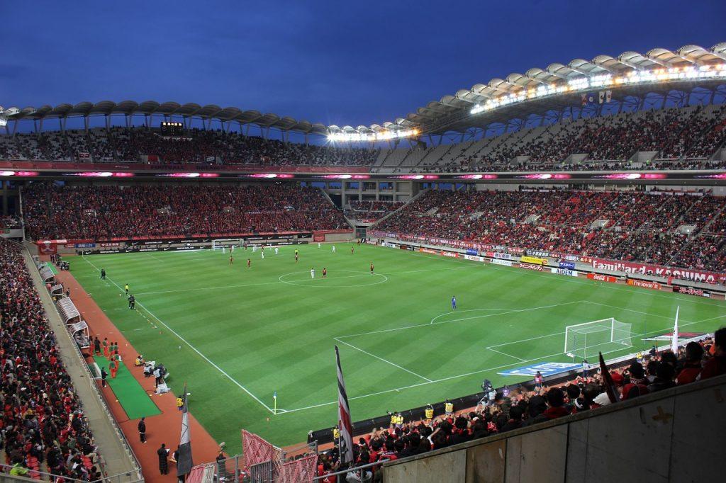 Arena med fotbollsplan och spelare